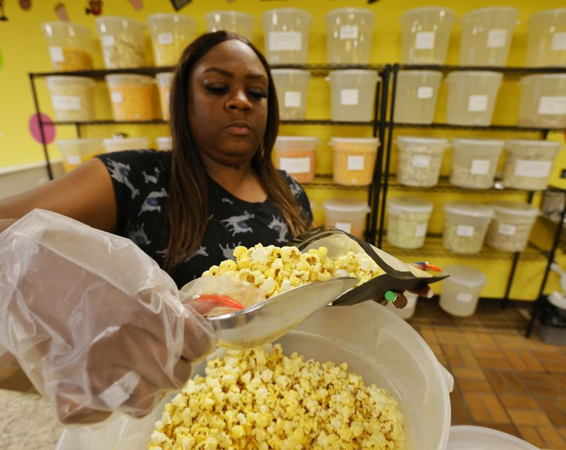 Marie Nelson scoops out popcorn for a customer at Nelson's Popcorn Land Tuesday, Sept. 21, 2021 on Pleasant Avenue in Fairfield. They have over forty varieties of popcorn and pretzels available to try before you buy. NICK GRAHAM / STAFF